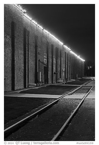 Railroad tracks and brick buildings at night, Stockyards. Fort Worth, Texas, USA (black and white)