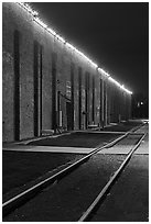 Railroad tracks and brick buildings at night, Stockyards. Fort Worth, Texas, USA ( black and white)
