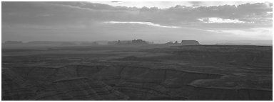Sunset over canyon and distant mesas. Monument Valley Tribal Park, Navajo Nation, Arizona and Utah, USA (Panoramic black and white)