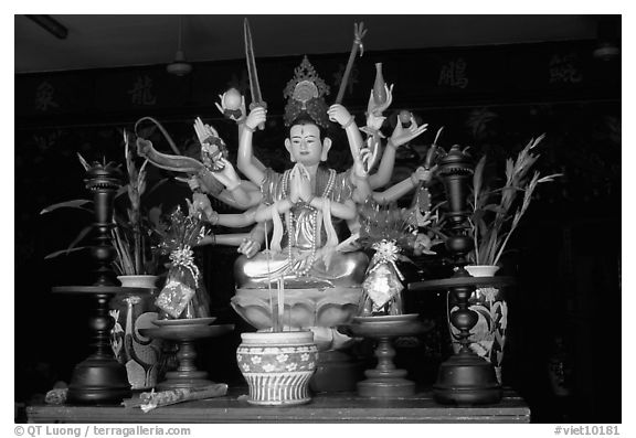Altar with a multiple-armed buddhist statue. Ho Chi Minh City, Vietnam (black and white)