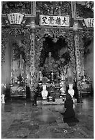 Woman praying at the altar. Ho Chi Minh City, Vietnam ( black and white)