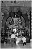 Men worshipping in front of a large Buddha state, Xa Loi pagoda. Ho Chi Minh City, Vietnam (black and white)