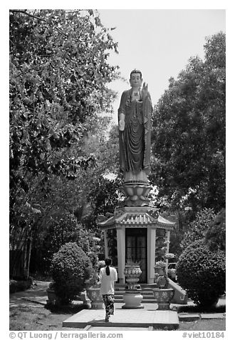 Woman praying under a large buddhist statue. Ho Chi Minh City, Vietnam