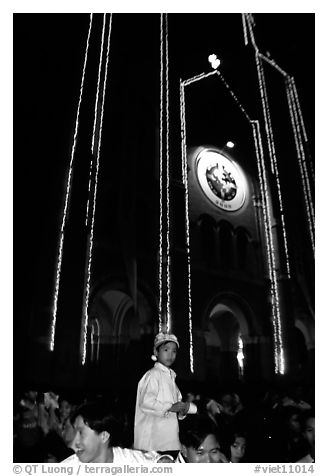 Child with christmas hat in front of St Joseph Cathedral on Christmas eve. Ho Chi Minh City, Vietnam (black and white)