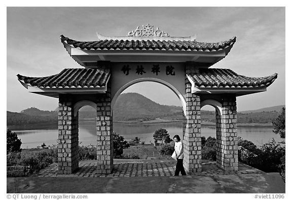 Pagoda gate with woman standing near lake. Da Lat, Vietnam (black and white)