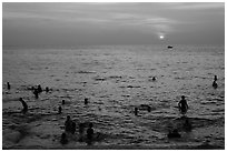 People bathing in Gulf of Thailand waters at sunset. Phu Quoc Island, Vietnam ( black and white)