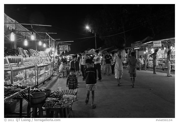 Shoppers walk past craft booth at night market. Phu Quoc Island, Vietnam (black and white)