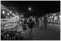 Shoppers walk past craft booth at night market. Phu Quoc Island, Vietnam ( black and white)