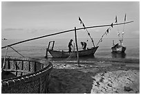 Fishermen pulling net onto skiff. Phu Quoc Island, Vietnam ( black and white)
