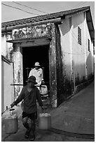 Workers carrying out containers of nuoc mam, Duong Dong. Phu Quoc Island, Vietnam ( black and white)