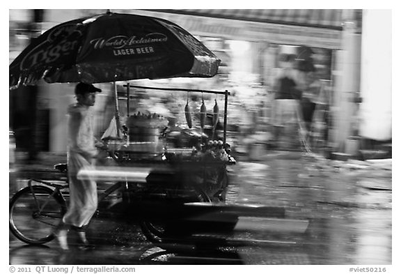 Man riding riding food cart in the rain. Ho Chi Minh City, Vietnam