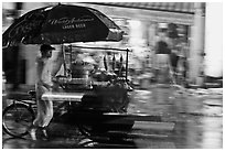 Man riding riding food cart in the rain. Ho Chi Minh City, Vietnam (black and white)