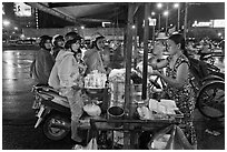 Women riding motorbikes buy sweet rice. Ho Chi Minh City, Vietnam (black and white)