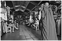Buddhist Monk walking into Ben Thanh Market. Ho Chi Minh City, Vietnam (black and white)