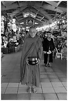 Buddhist Monk doing alms round in Ben Thanh Market. Ho Chi Minh City, Vietnam (black and white)