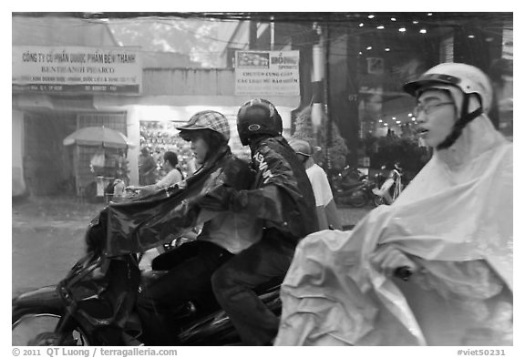 Motorcycle riders during afternoon mooson. Ho Chi Minh City, Vietnam (black and white)