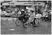 Women riding bicyles in the rain. Ho Chi Minh City, Vietnam (black and white)