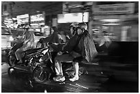Motorcyle riders at night, dressed for the rain. Ho Chi Minh City, Vietnam (black and white)