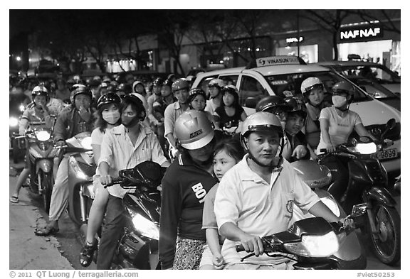 Riders waiting for traffic light at night. Ho Chi Minh City, Vietnam (black and white)
