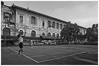 Men play tennis in front of colonial-area courthouse. Ho Chi Minh City, Vietnam (black and white)