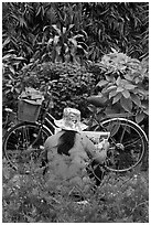 Woman reading newspaper next to bicycle in park. Ho Chi Minh City, Vietnam (black and white)