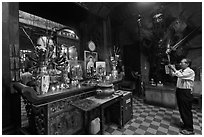 Man in prayer, with fierce statue of general behind, Jade Emperor Pagoda, district 3. Ho Chi Minh City, Vietnam (black and white)