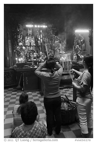 Women offering incense to Jade Emperor figure, Phuoc Hai Tu pagoda, district 3. Ho Chi Minh City, Vietnam (black and white)