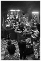 Women offering incense to Jade Emperor figure, Phuoc Hai Tu pagoda, District 3. Ho Chi Minh City, Vietnam ( black and white)