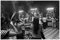 Worshipping at altar with  Jade Emperor and Four Big Diamonds, Chua Ngoc Hoang, district 3. Ho Chi Minh City, Vietnam (black and white)