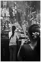 Women holding incense sticks, Phuoc Hai Tu pagoda, District 3. Ho Chi Minh City, Vietnam (black and white)