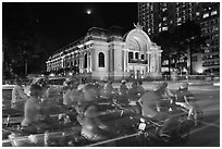 Motorcycles and Opera House at night. Ho Chi Minh City, Vietnam (black and white)