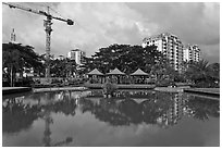 Reflecting pool, completed residential buildings, and crane, Phu My Hung, District 7. Ho Chi Minh City, Vietnam (black and white)