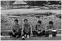 Uniformed students eating in front of backdrop depicting rural landscape. Ho Chi Minh City, Vietnam (black and white)