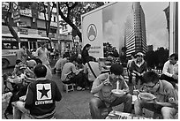 Uniformed students eating breakfast in front of backdrop depicting high rise in construction. Ho Chi Minh City, Vietnam ( black and white)