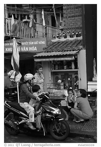 Neighborhood chat in front of street altar. Ho Chi Minh City, Vietnam