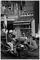 Neighborhood chat in front of street altar. Ho Chi Minh City, Vietnam (black and white)