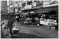 Woman carrying goods on street market. Ho Chi Minh City, Vietnam (black and white)
