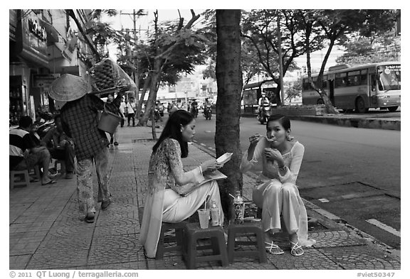 Women elegantly dressed in ao dai eating on the street. Ho Chi Minh City, Vietnam (black and white)