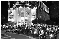 Dense motorcycle traffic in front of Saigon Center at night. Ho Chi Minh City, Vietnam (black and white)