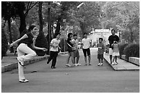 Young woman playing footbag as audience watches, Cong Vien Van Hoa Park. Ho Chi Minh City, Vietnam (black and white)