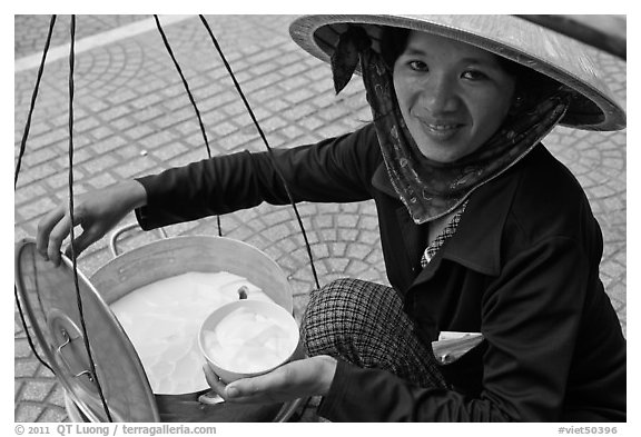 Woman smiling while handling bowl of soft tofu. Ho Chi Minh City, Vietnam (black and white)