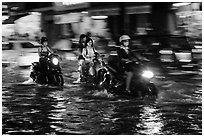 Women riding motorcyles at night in water. Ho Chi Minh City, Vietnam (black and white)