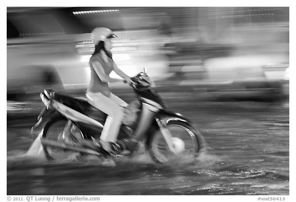 Woman riding on water-filled street, and light streaks. Ho Chi Minh City, Vietnam (black and white)