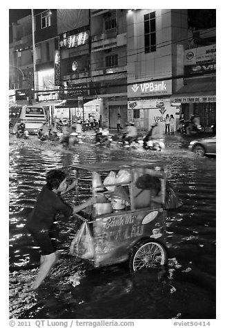 Vendor pushing foot car into the water at night. Ho Chi Minh City, Vietnam (black and white)