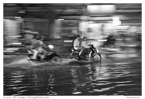 Motorcycles riding through the water on street with motion. Ho Chi Minh City, Vietnam (black and white)