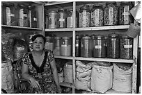 Woman with jars of traditional medicinal supplies. Cholon, Ho Chi Minh City, Vietnam (black and white)