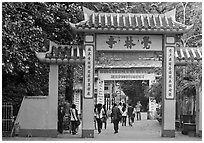 People walking through gates, Giac Lam Pagoda, Tan Binh District. Ho Chi Minh City, Vietnam ( black and white)