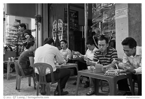 Men eating breakfast on the street. Ho Chi Minh City, Vietnam (black and white)