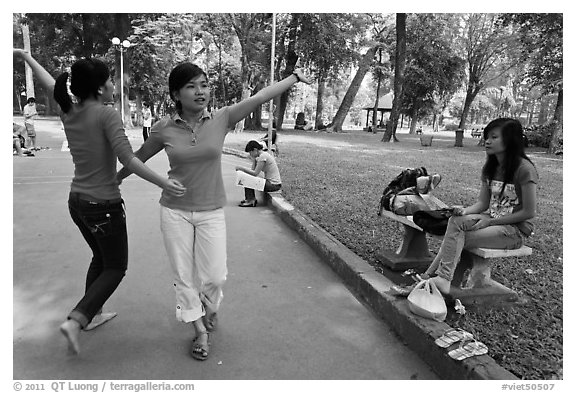 Young women dancing to sound of mobile phone, Tao Dan Park. Ho Chi Minh City, Vietnam (black and white)
