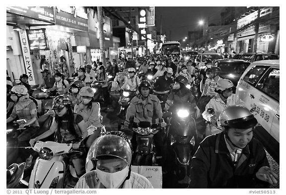 Street packed with motorcycles and vehicles at dusk. Ho Chi Minh City, Vietnam
